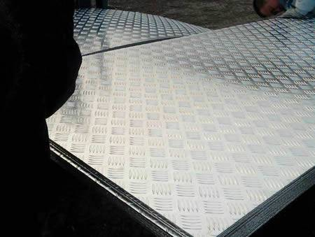 Many rectangular aluminum checker plates are in workshop.