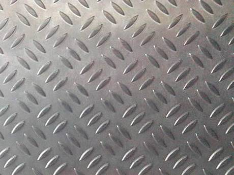 A piece of aluminum checker plate with short rice shaped projections.