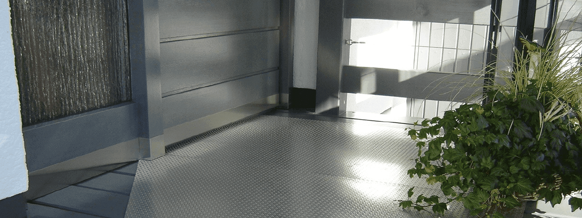 high strength alloy steel hot-rolled checker plates for flooring of a large room, and a large pot of green plants on the ground.