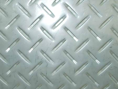 A piece of stainless steel checker plate with raised long strip projections.