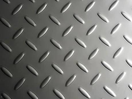 A piece of stainless steel checker plate with raised small rice projections.