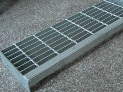 A stair tread steel grating with vertical strip nosing.