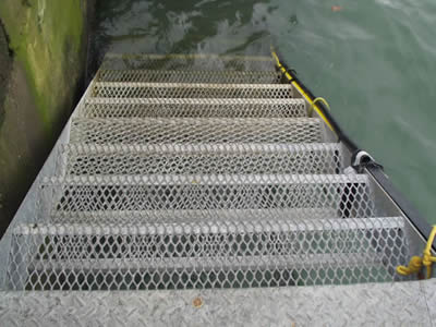 The bottom of a stair made of expanded metal grating connects a river.