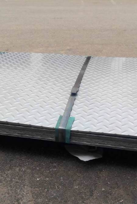 Many pieces of stainless steel checker plates are packed with steel strips.