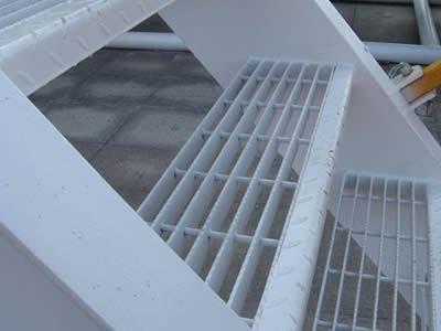 Several swage-locked steel grating treads form a stair.